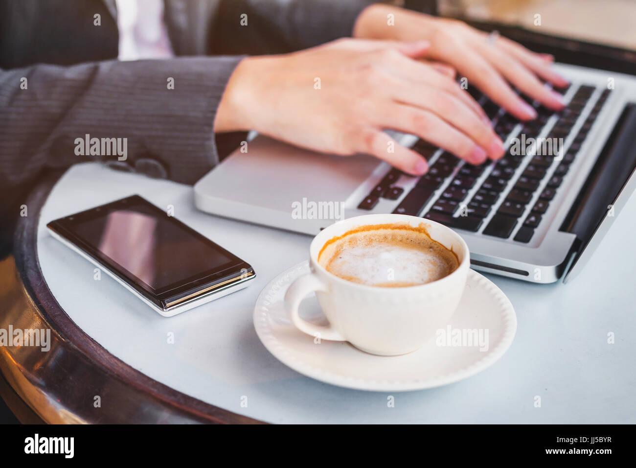 Travailler sur ordinateur en ligne femme, consulter ses e-mails sur l'ordinateur portable dans un café, Photo Stock