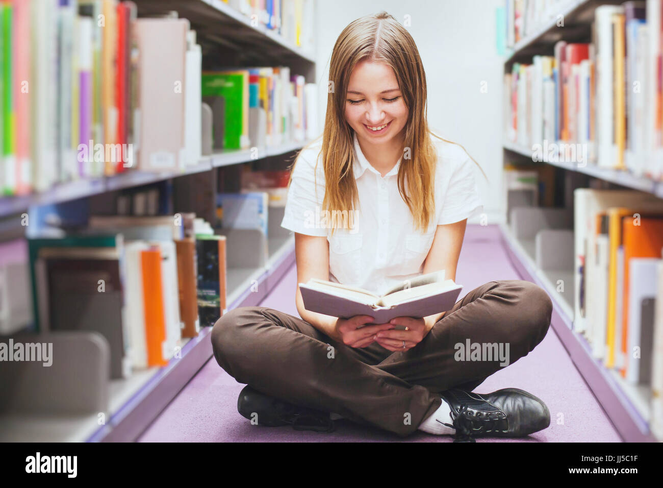 Student reading book in the library, smiling happy woman, arrière-plan de l'éducation Photo Stock