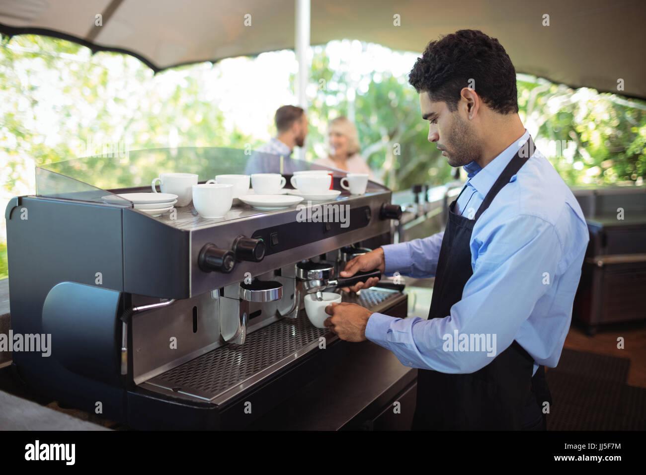 Ce serveur à partir de la tasse de café machine à expresso dans le Photo Stock