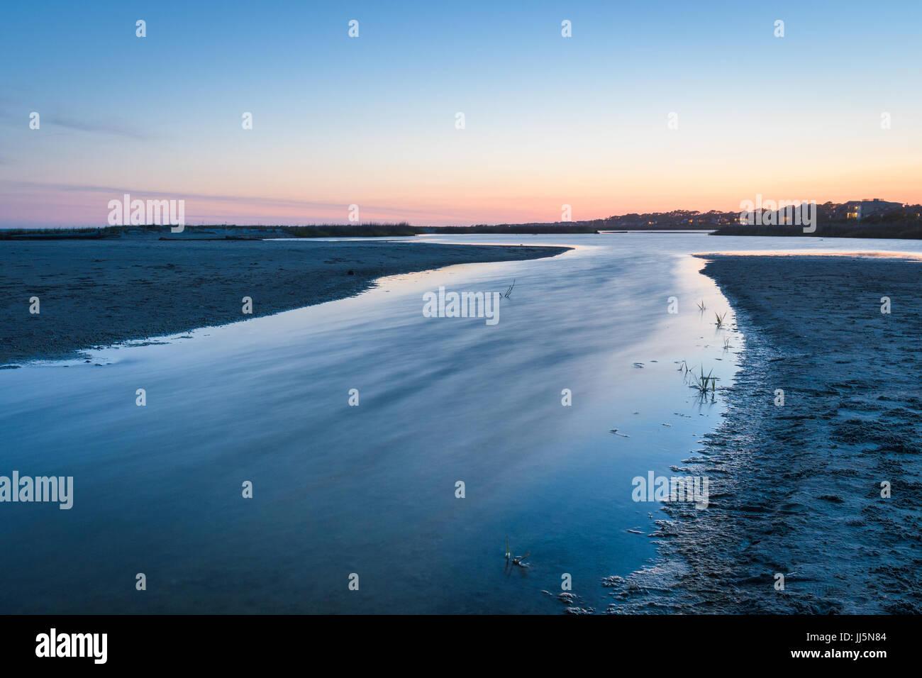 Rivière à marée descend sur la plage au lever du soleil. Photo Stock