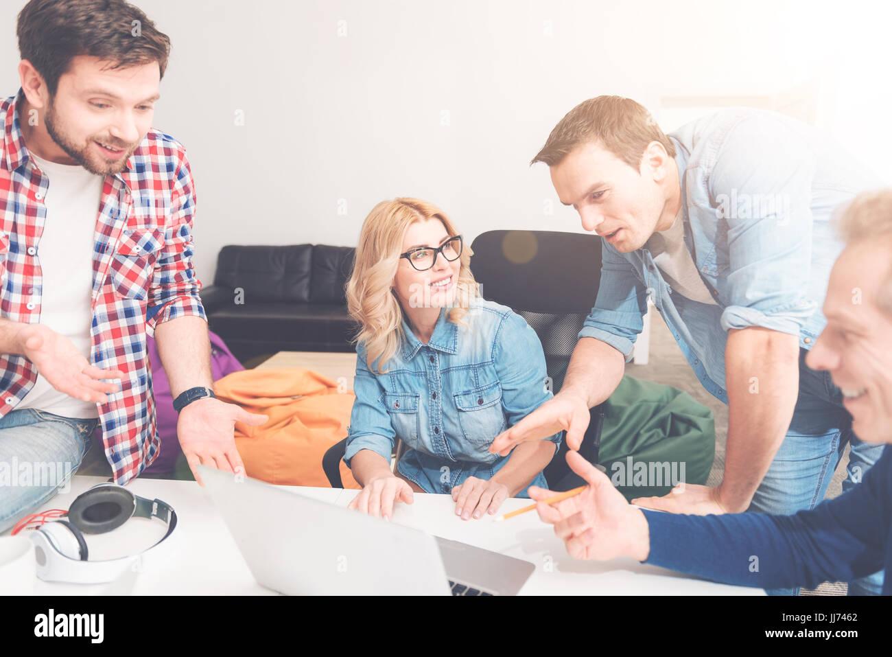 Collègues positifs à l'aide d'ordinateur portable dans le bureau Photo Stock