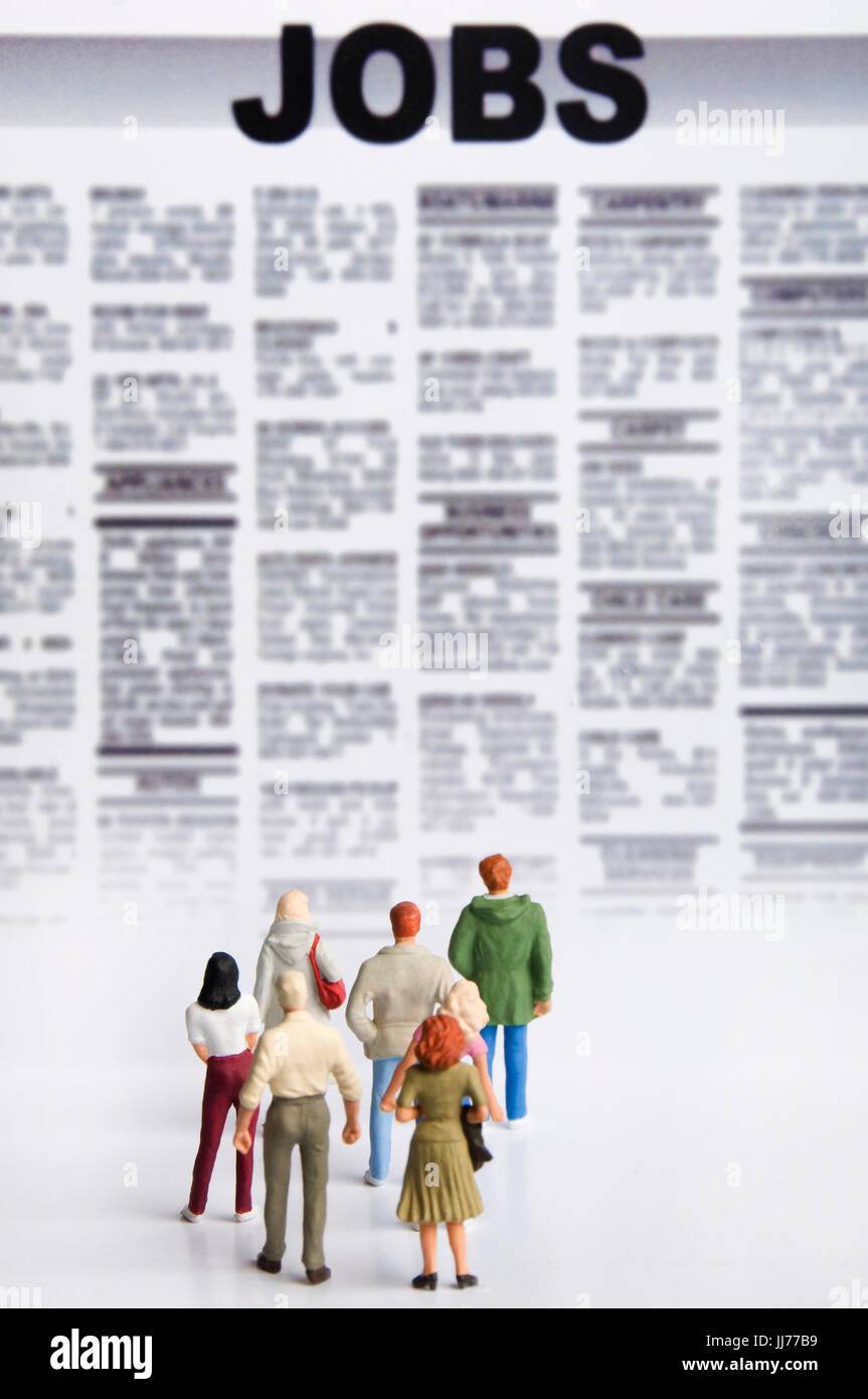 Miniatures comme concept pour les chômeurs en font d'emplois à la recherche d'annonces immobilières Photo Stock