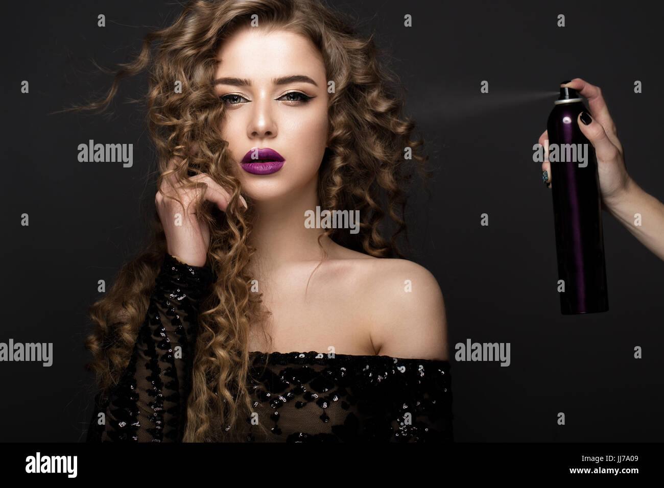 b4eb87a1099 Belle brune modèle avec maquillage classique et bouteille de produits pour  les cheveux. beauté visage.