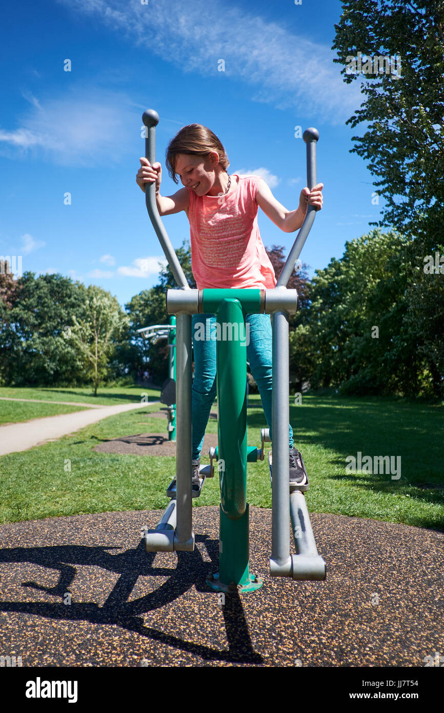 Une jeune fille utilise l'équipement d'exercice en plein air d'exercer dans un parc sur une journée Photo Stock
