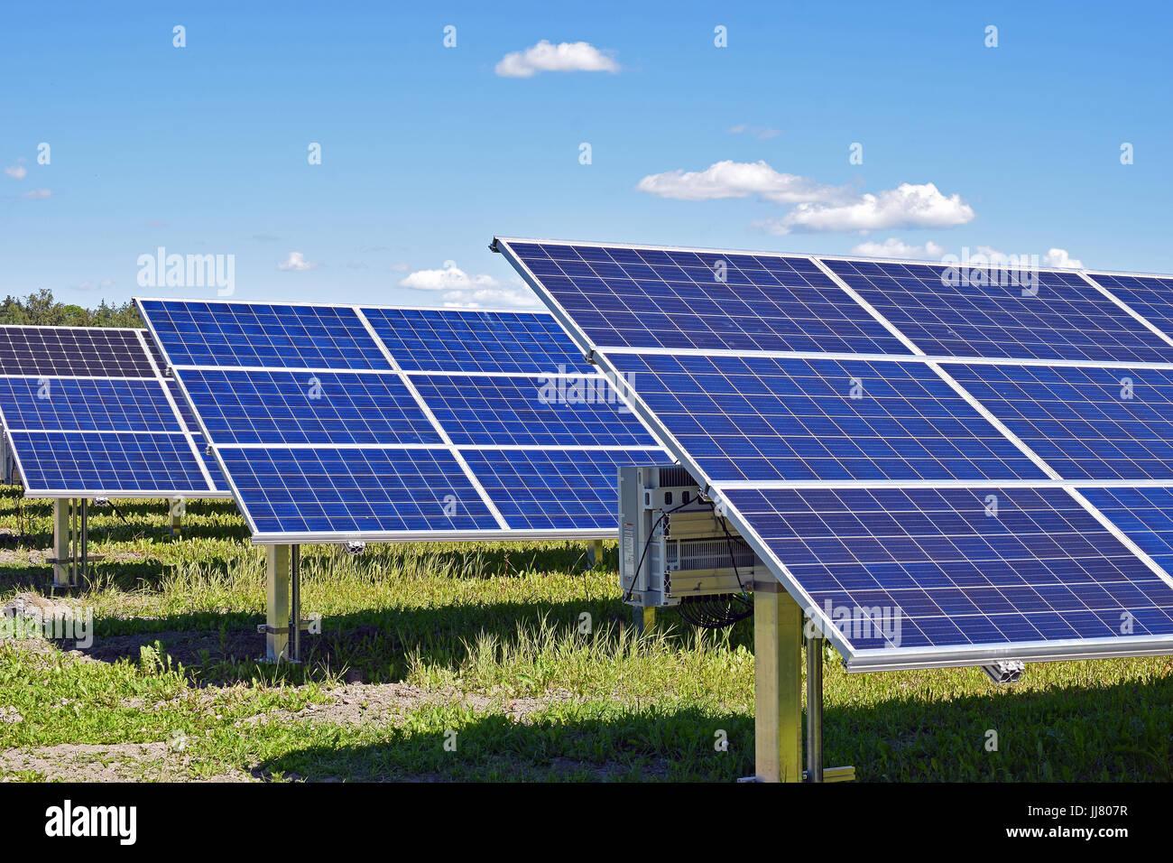 Panneaux solaires sur terrain. Ciel clair avec quelques petits nuages sur l'arrière-plan. Photo Stock
