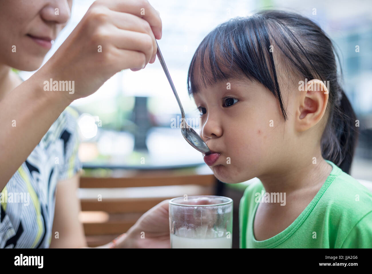Chinois asiatique peu girl drinking beverage at outdoor restaurant Photo Stock