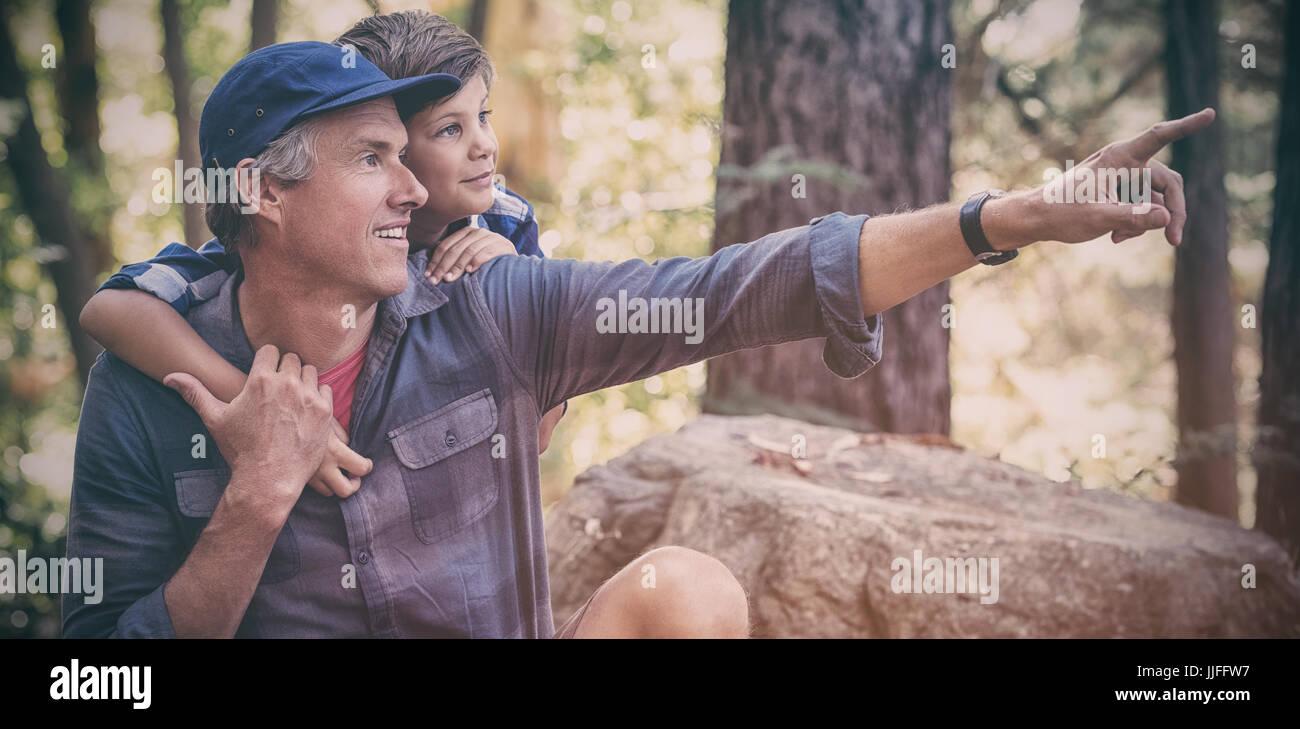 Père montrant quelque chose de curieux garçon lors d'une randonnée en forêt Photo Stock
