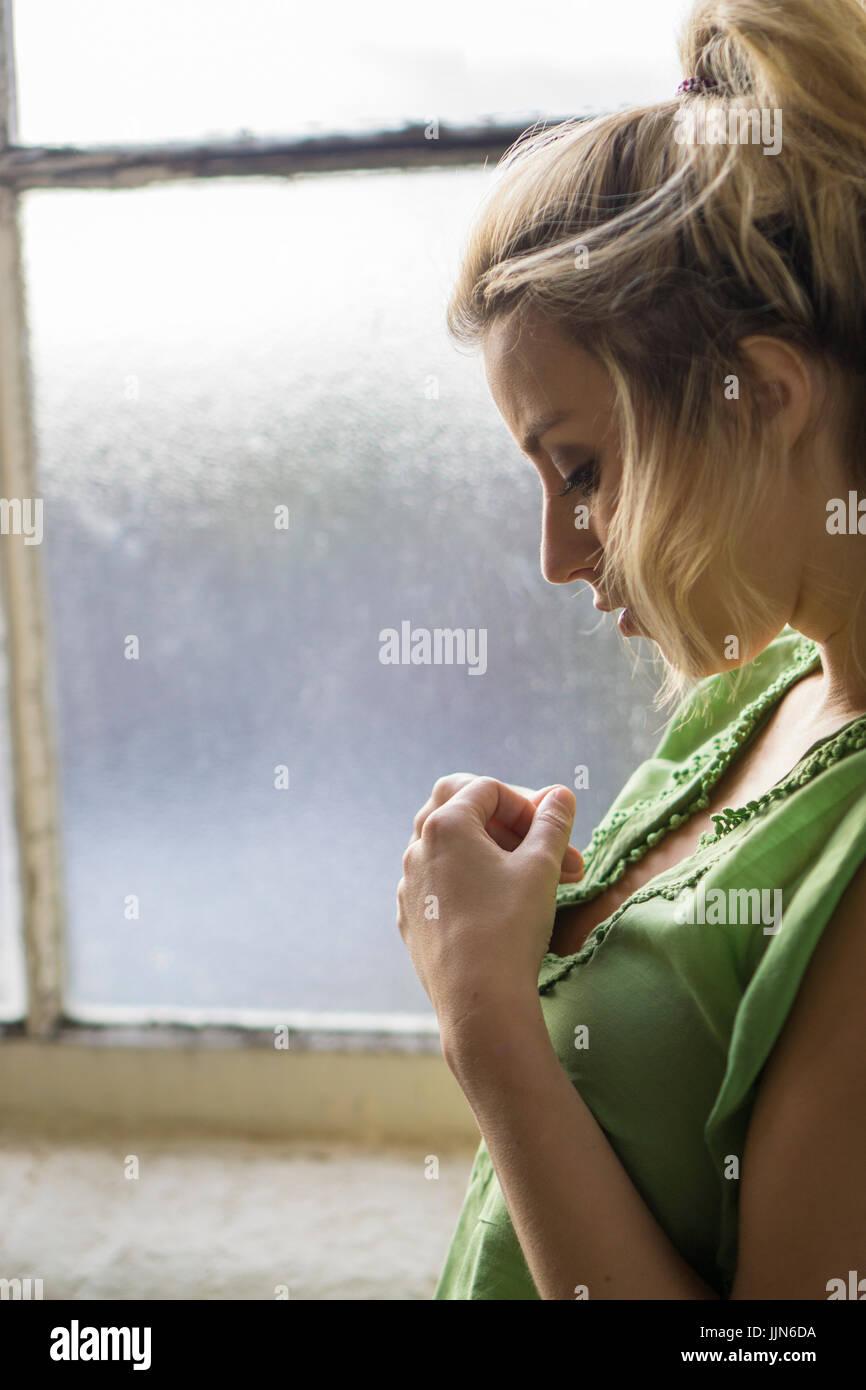 Vue latérale d'un sad young woman standing by la fenêtre Photo Stock