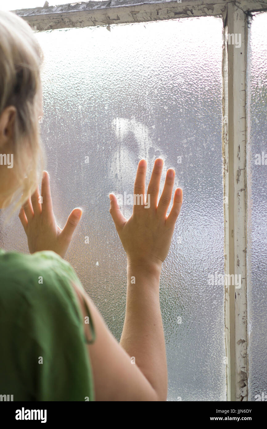 Vue arrière d'une jeune femme blonde debout près de la fenêtre Photo Stock