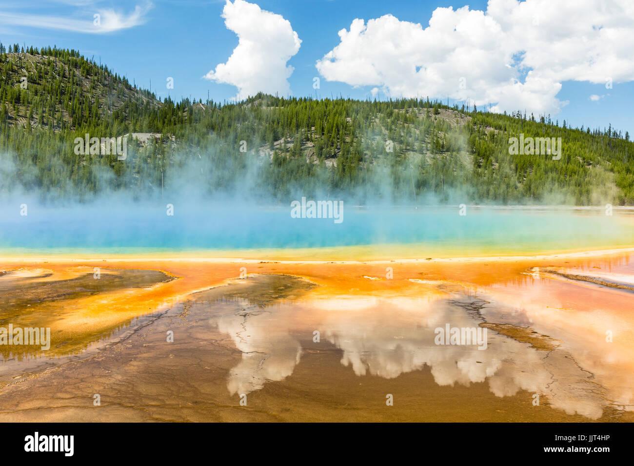 Les nuages reflètent dans les couleurs arc-en-ciel vif du Grand Prismatic Spring dans le Parc National de Yellowstone, Banque D'Images