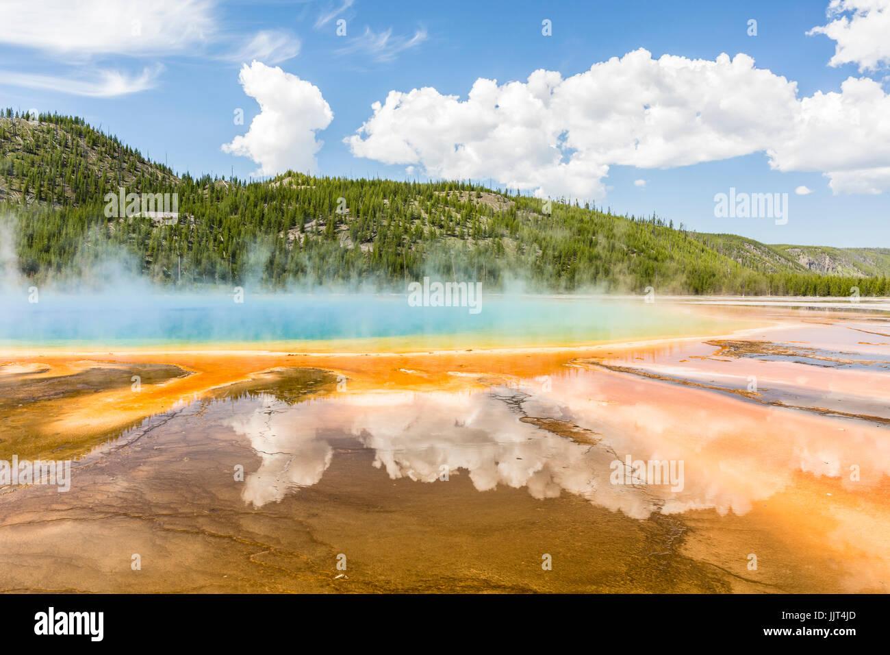 Les nuages reflètent dans les couleurs arc-en-ciel vif du Grand Prismatic Spring dans le Parc National de Yellowstone, Wyoming Banque D'Images