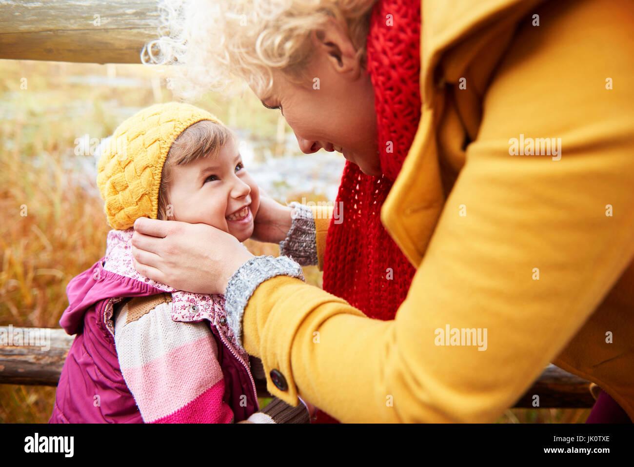 Mère de caresser les joues des filles à froid Photo Stock