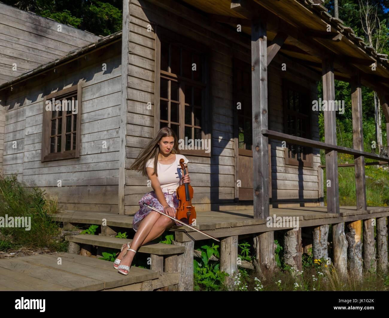 Le Porche De La Maison pays-girl avec violon assis sur le porche de la maison en bois