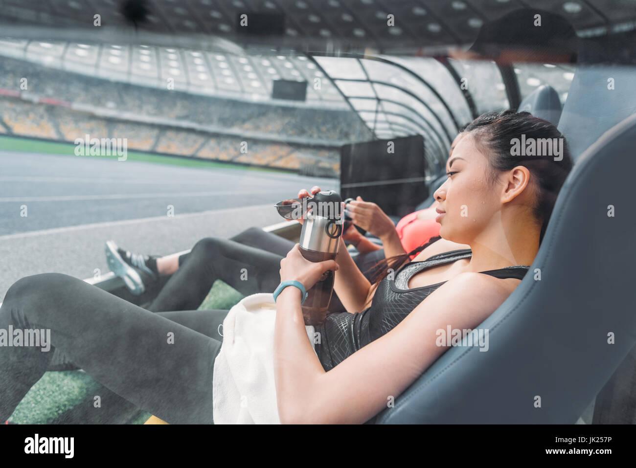 Les jeunes femmes remise en forme fatigué dans les vêtements de sport au  repos dans les sièges du stade edd200d87f5
