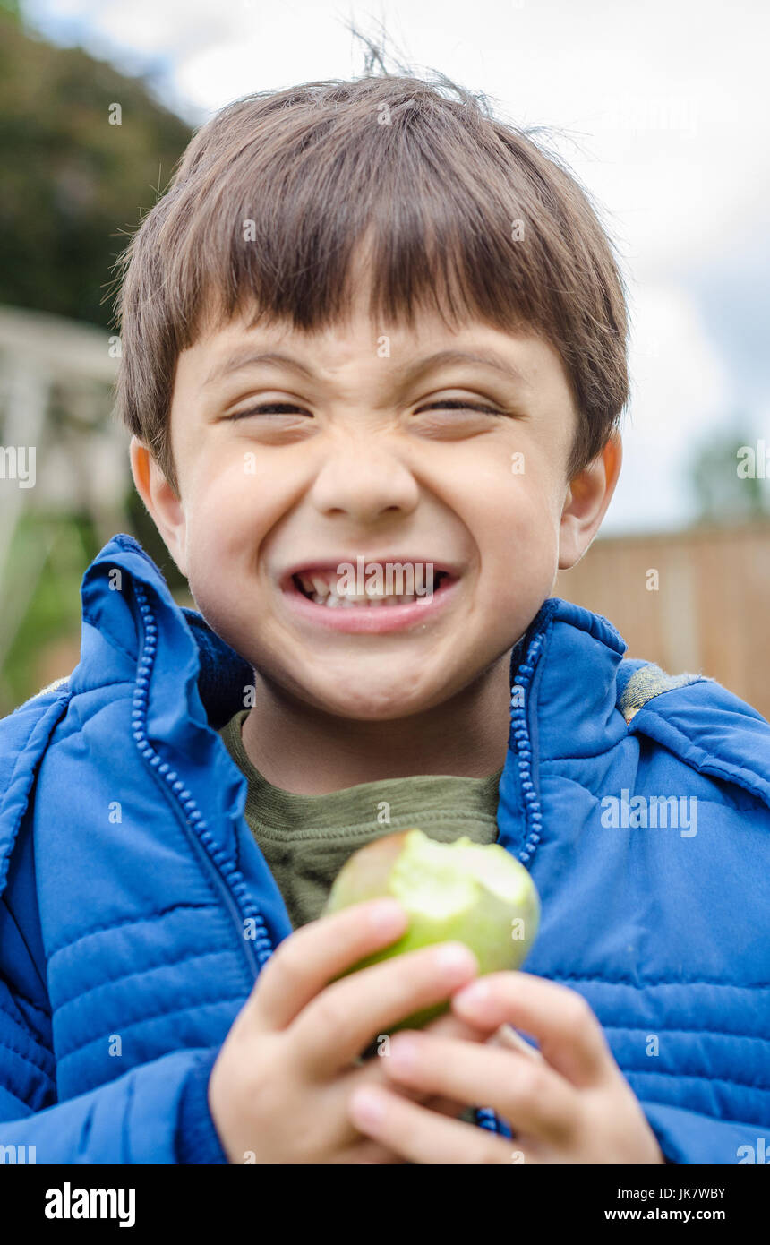 Un garçon mangeant une pomme cultivée accueil dans le jardin arrière. Photo Stock