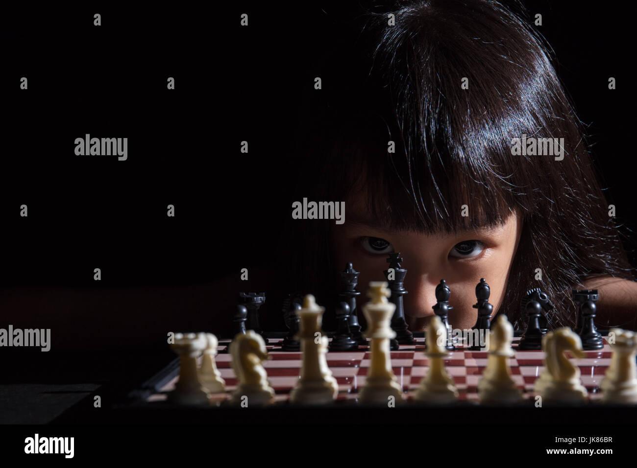 Petite fille asiatique chinois jouant aux échecs dans l'arrière-plan noir isolé Photo Stock