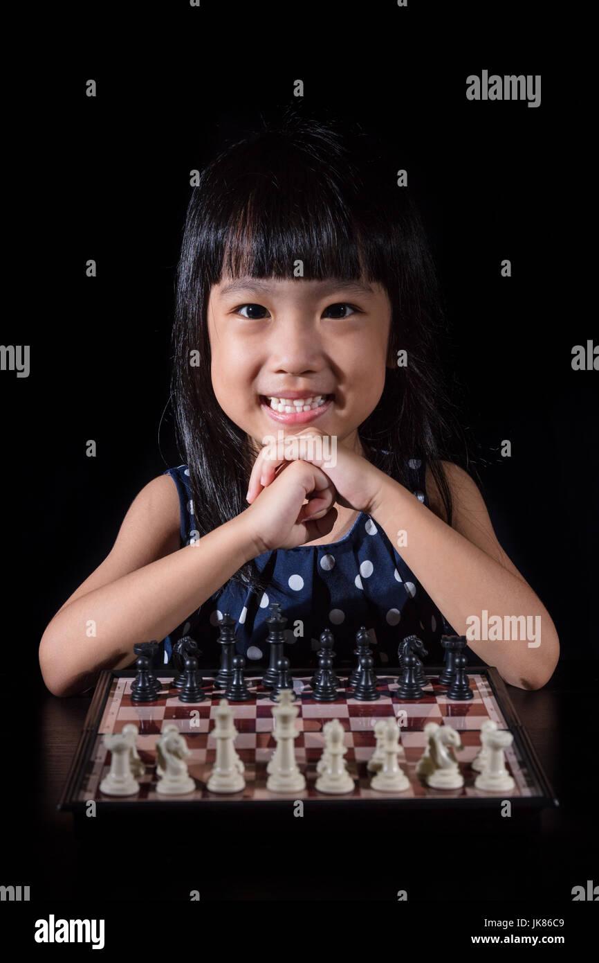 Petite fille asiatique chinois jouant aux échecs dans l'arrière-plan noir isolé Banque D'Images