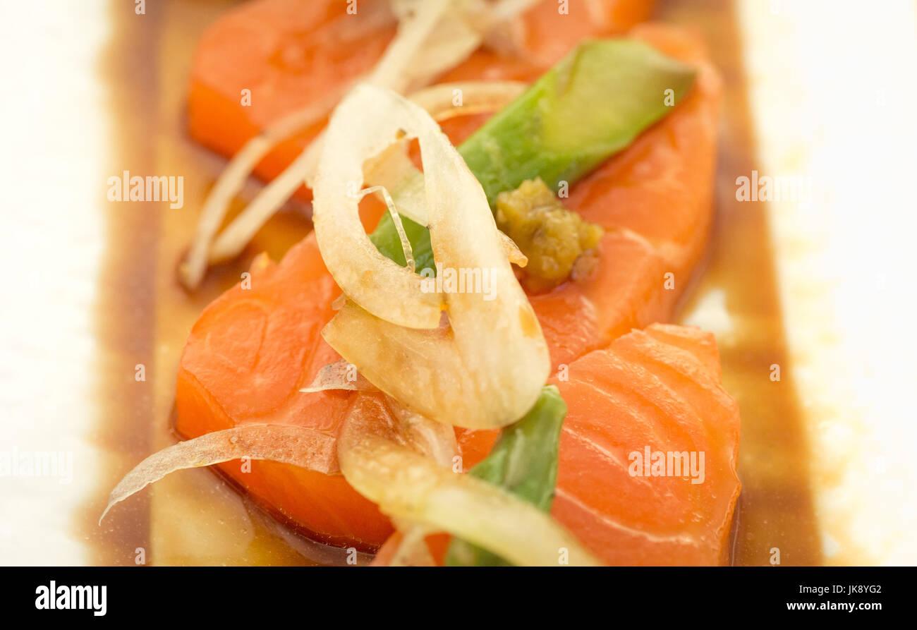 Sashimi de saumon aux asperges et l'oignon sur la plaque, prêt à manger. Photo Stock