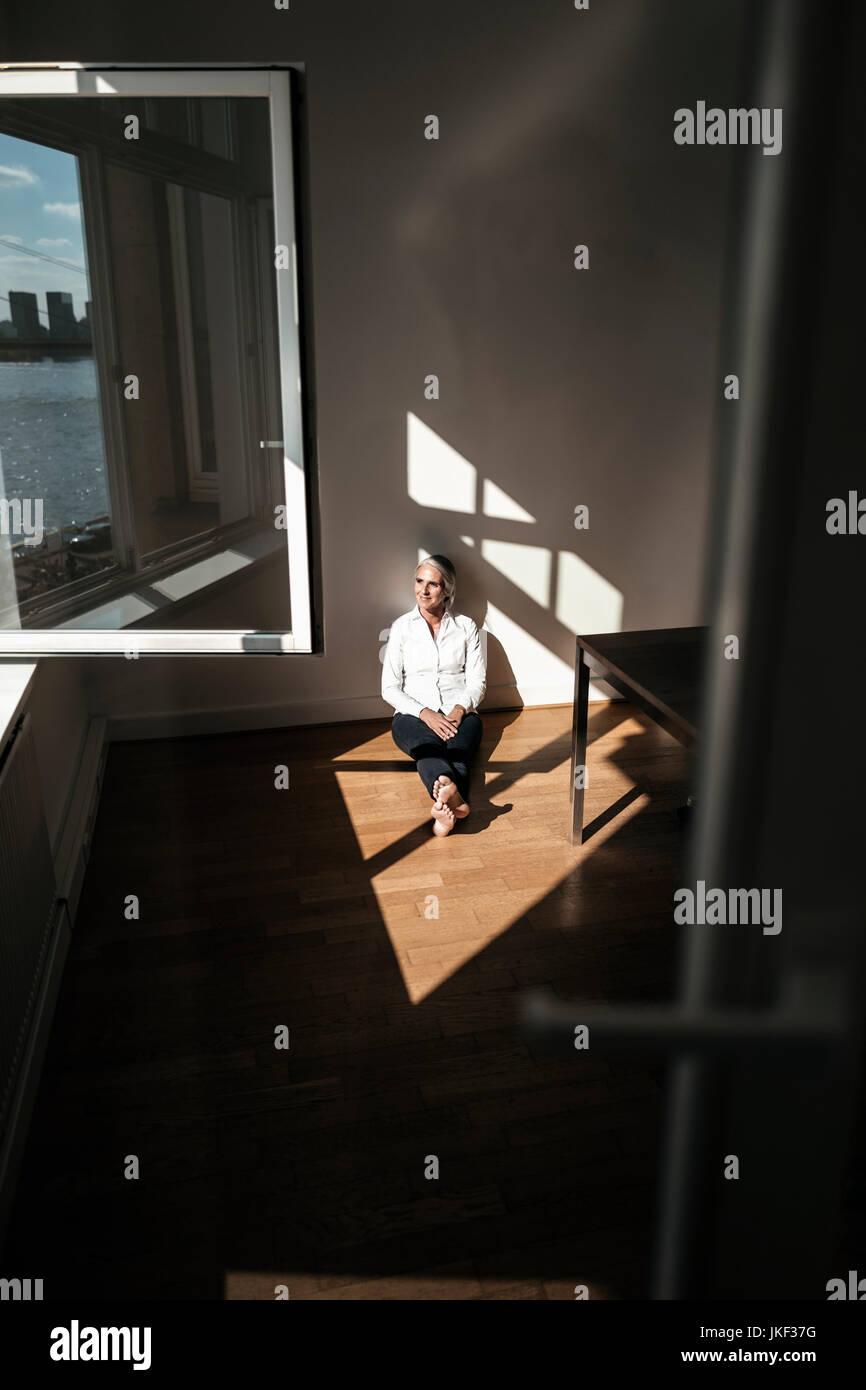 Businesswoman sitting on floor in office Photo Stock