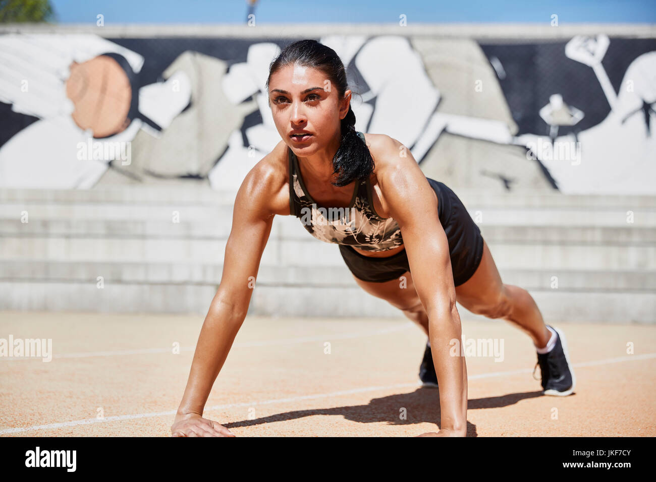 Monter woman doing pushups outdoors Photo Stock
