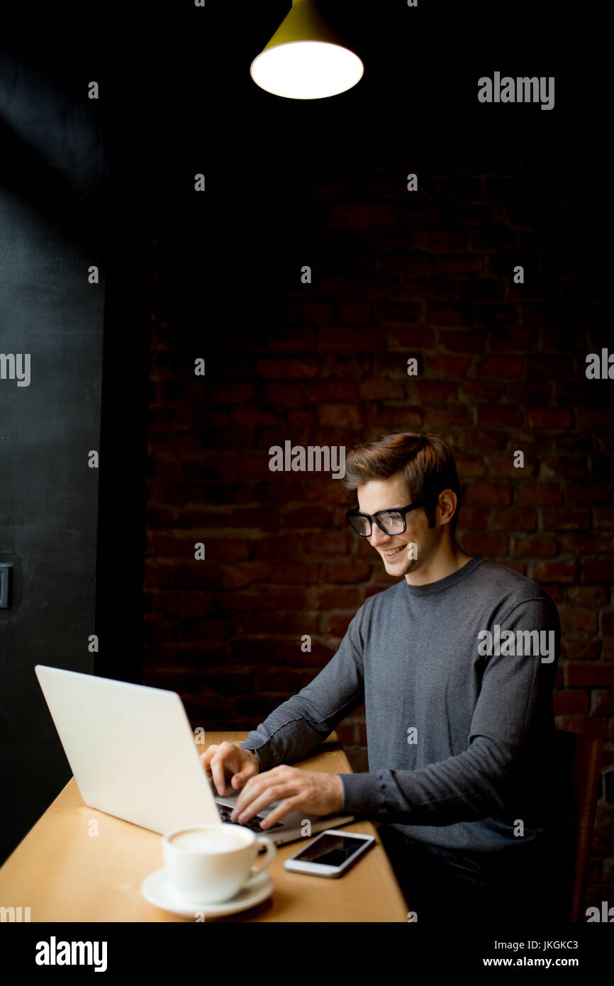 Portrait of a young man using laptop in the coffee shop Photo Stock