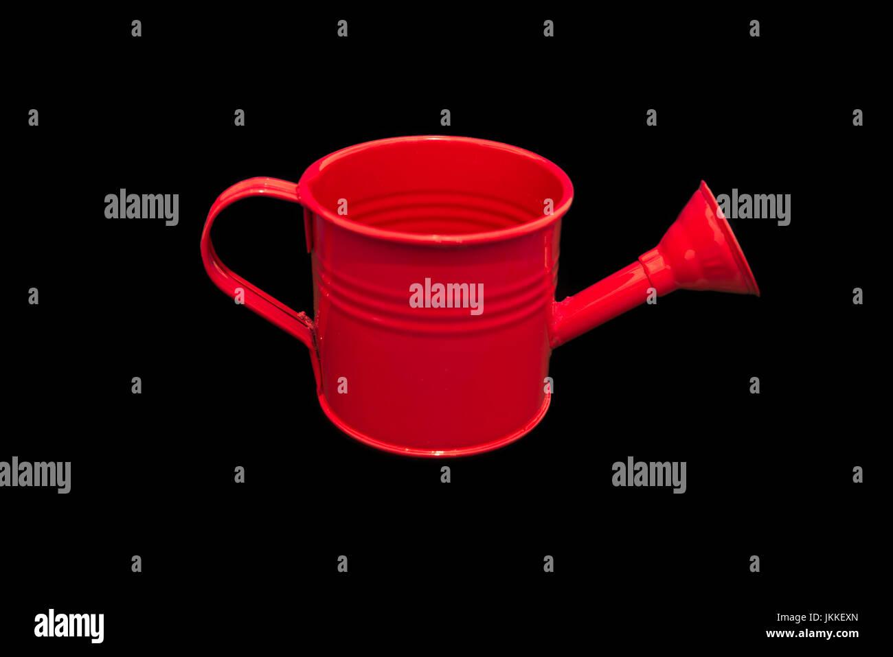 Arrosoir rouge isolé sur fond noir. L'image est propre et lumineux et centré dans l'image avec Photo Stock