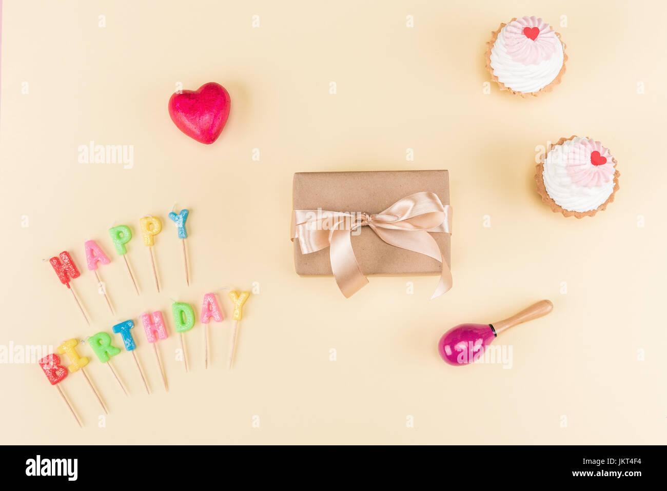 Vue de dessus de joyeux anniversaire lettrage, enveloppe avec du ruban et des petits gâteaux délicieux Photo Stock