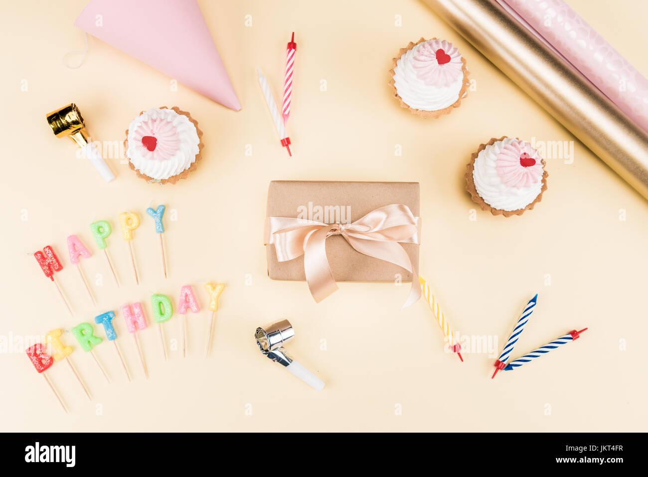 Vue de dessus de joyeux anniversaire lettrage, enveloppe avec ruban, gâteaux et cartes colorées sur rose, Photo Stock