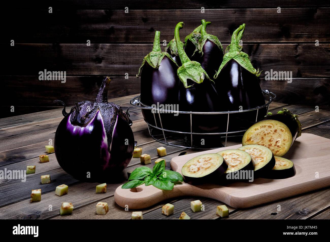 Close up of fresh ensemble violet aubergine et tranchées sur une table en bois vieilli. Banque D'Images