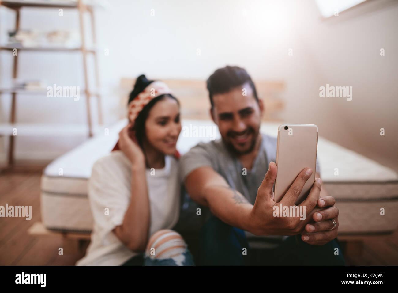Coup de jeune couple assis à la maison et en tenant avec selfies téléphone mobile. L'accent sur Photo Stock