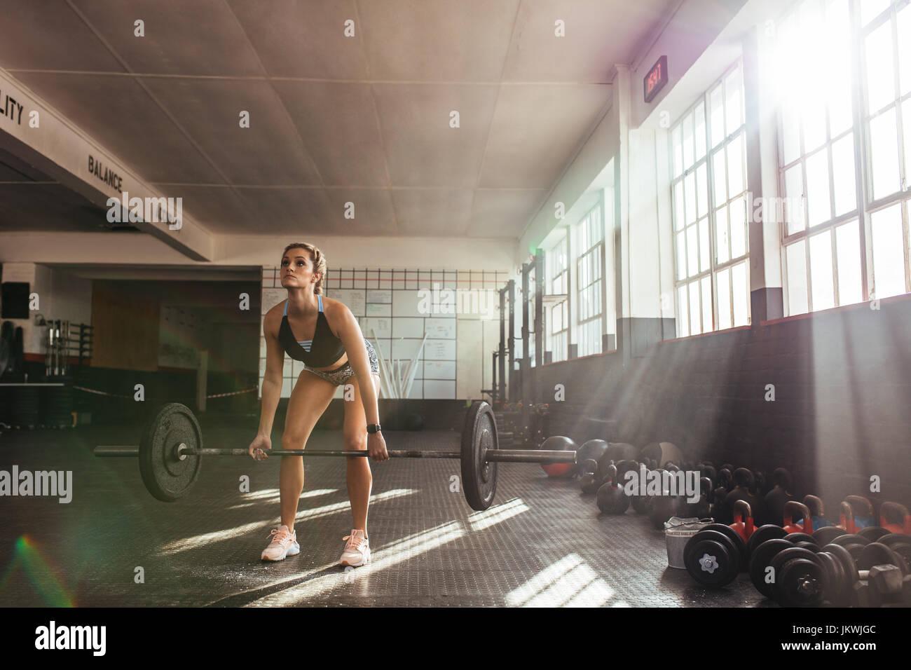 Les poids lourds de levage femme à la salle de sport pour l'entraînement musculaire. L'exercice Photo Stock