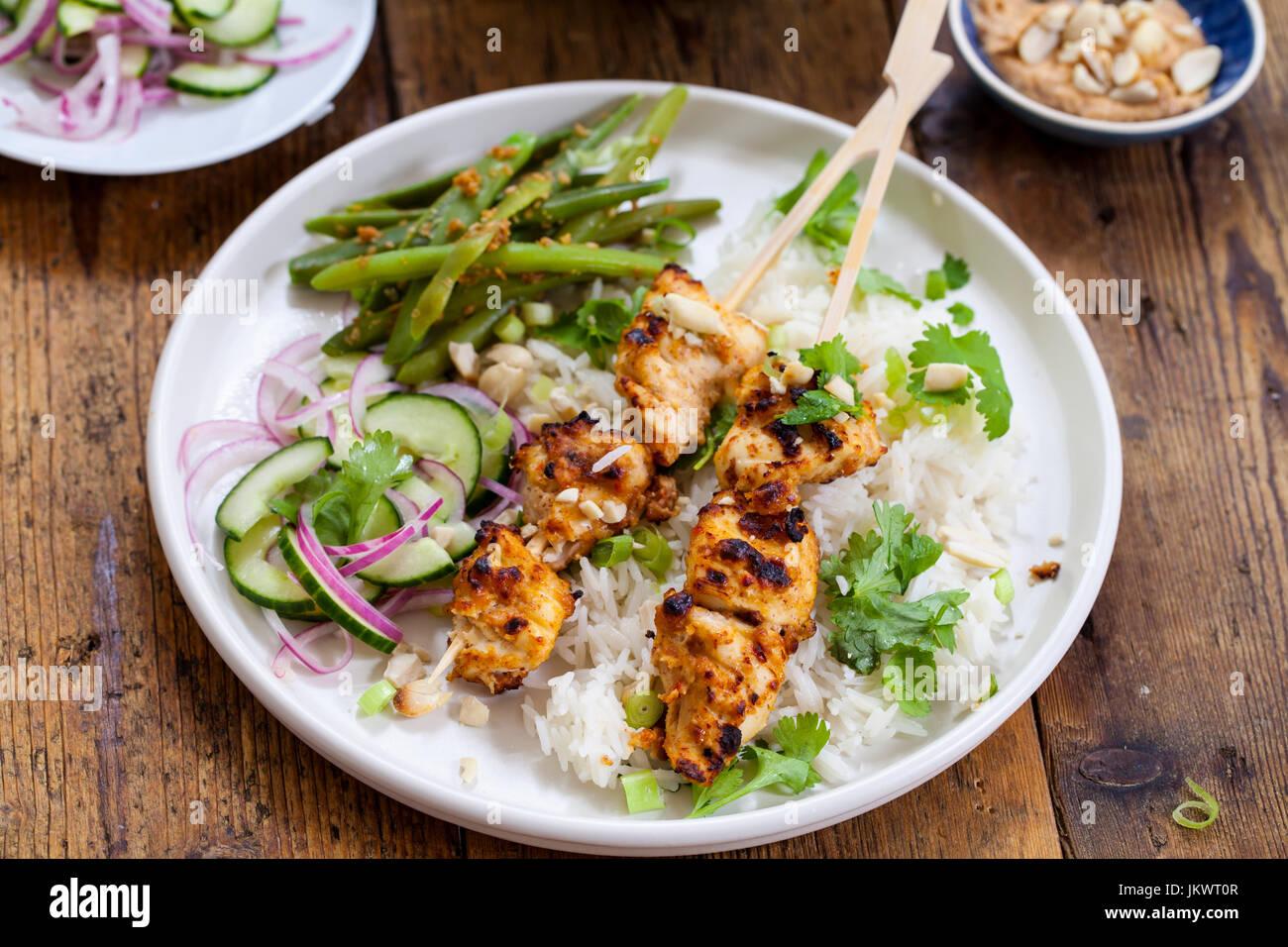 Brochettes Satay de poulet avec riz, salade de concombre et de haricots verts Photo Stock