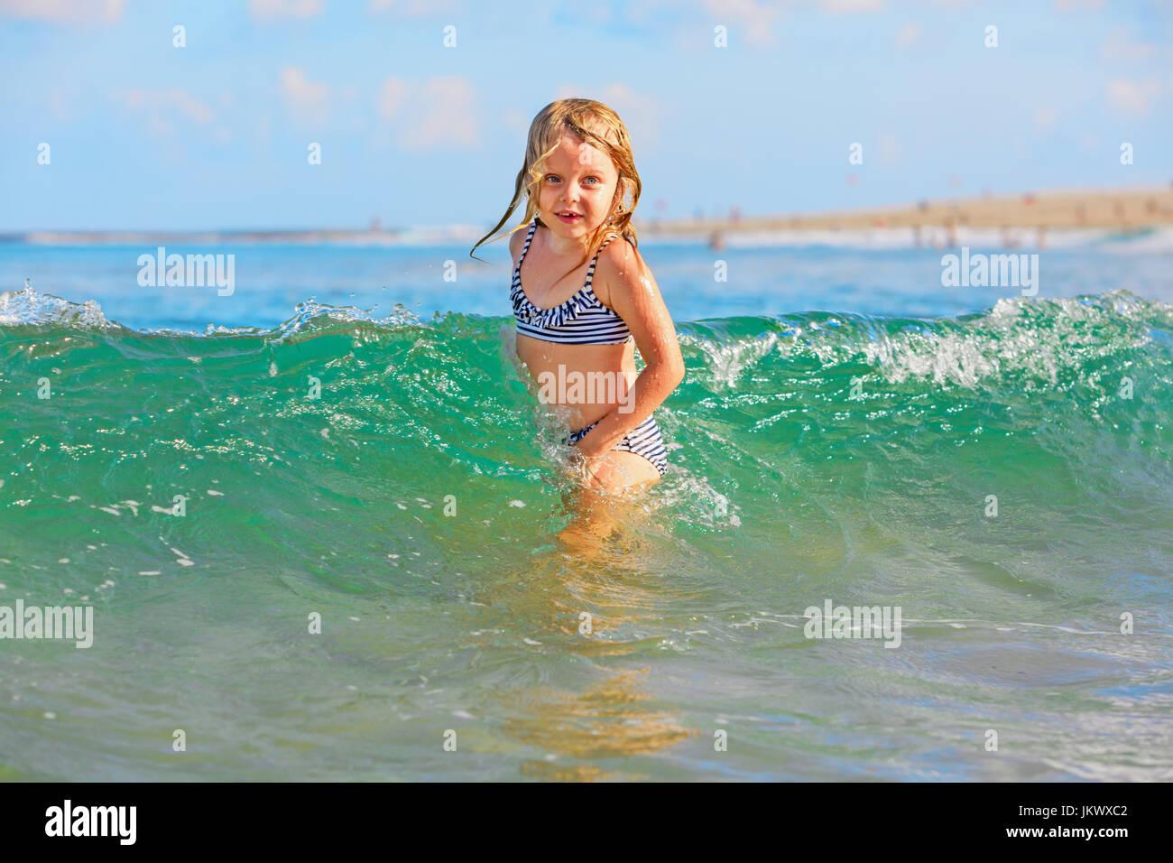 Vie de famille heureuse. Baby Girl splashing et sauter avec plaisir dans les vagues déferlantes. Billet d'été, Photo Stock