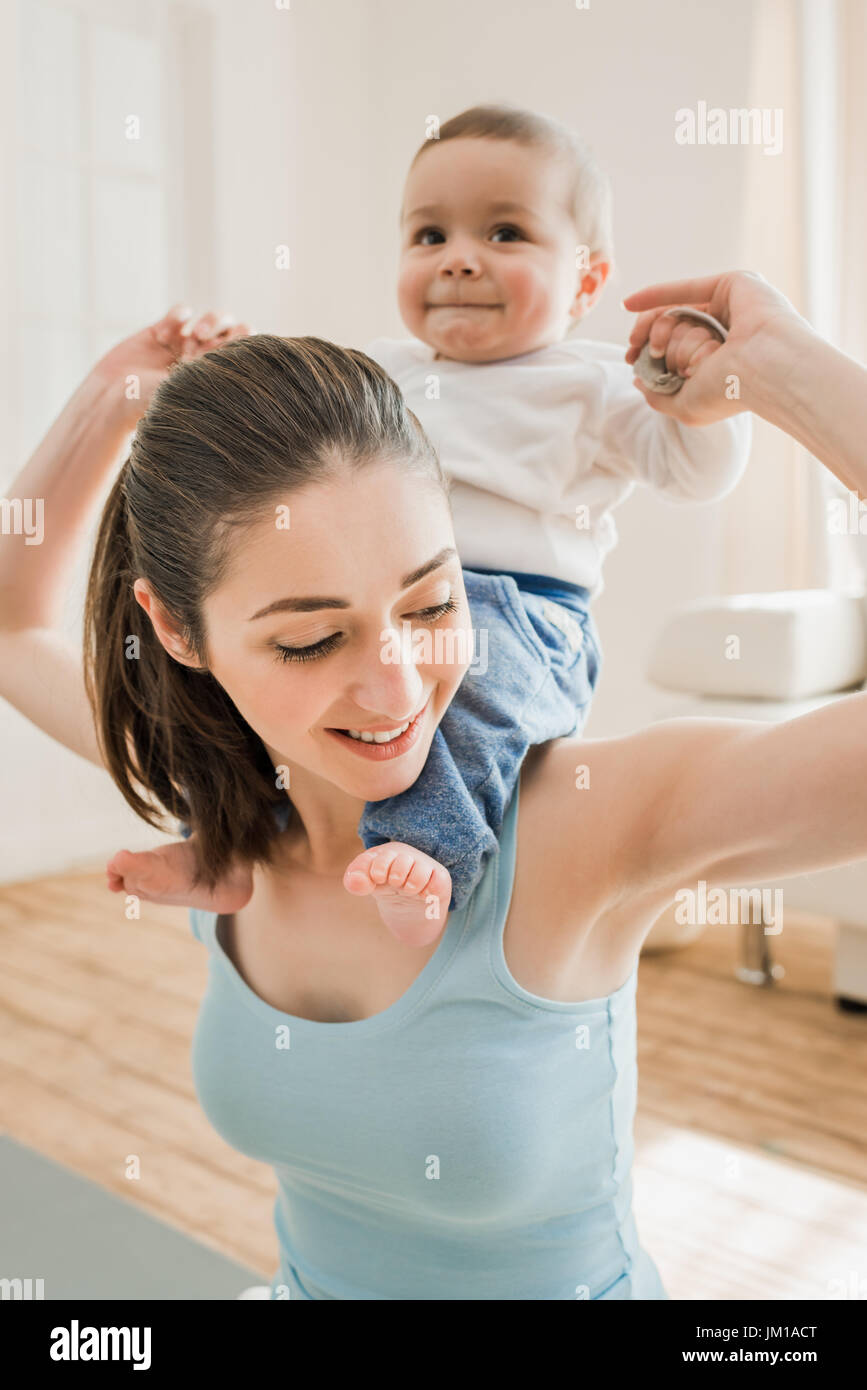 Portrait de jeune mère portant son fils à la maison de ferroutage Photo Stock