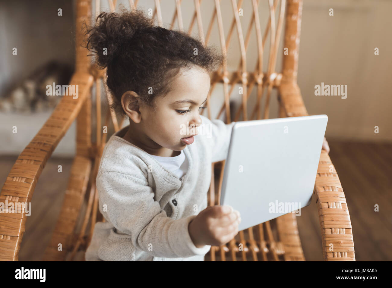 Adorable petit african american girl using digital tablet et assis sur un fauteuil à bascule à la maison Photo Stock