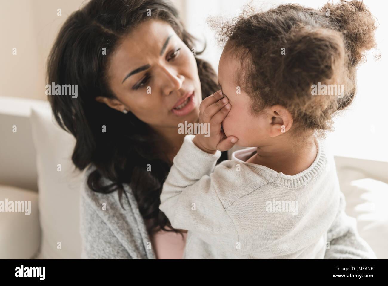 Mère regardant jolie petite fille pleurer à la maison Photo Stock