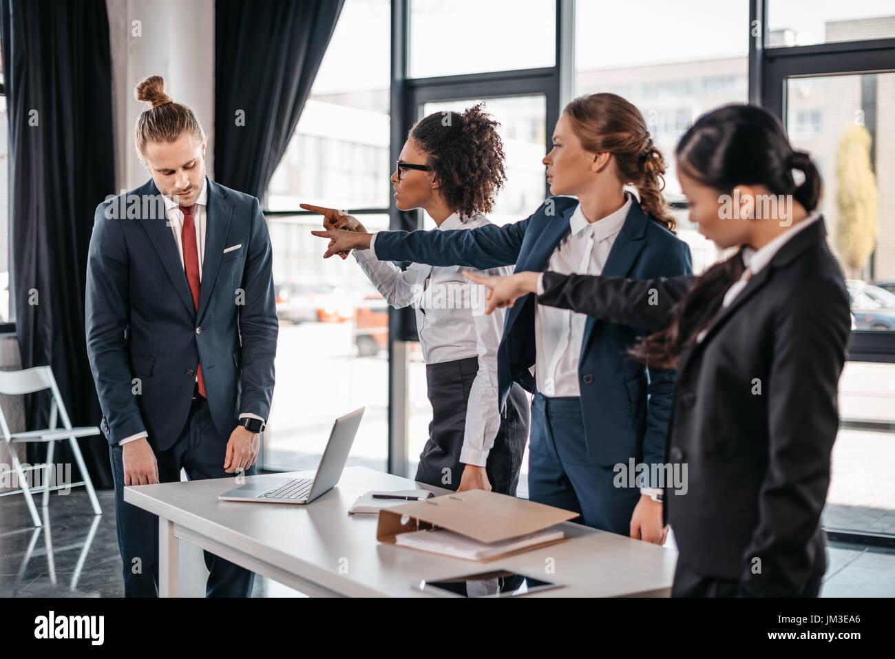 Trois jeunes femmes en colère avec les doigts pointant à upset businessman in office, réunion de l'équipe business concept Photo Stock
