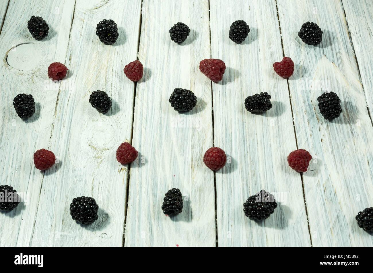 Blackberry et les framboises. sont disposés en une ligne. Vue d'en haut. Fruits rouges sur un fond blanc. Photo Stock