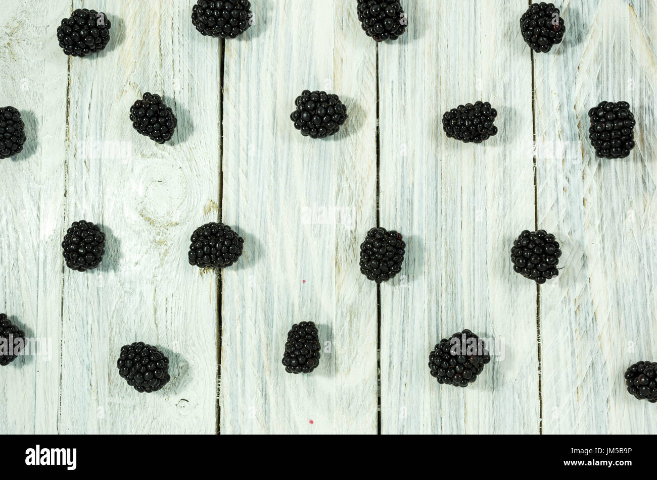 Blackberry sont disposés en une ligne. Mise à plat. Fruits rouges sur un fond blanc. Photo Stock