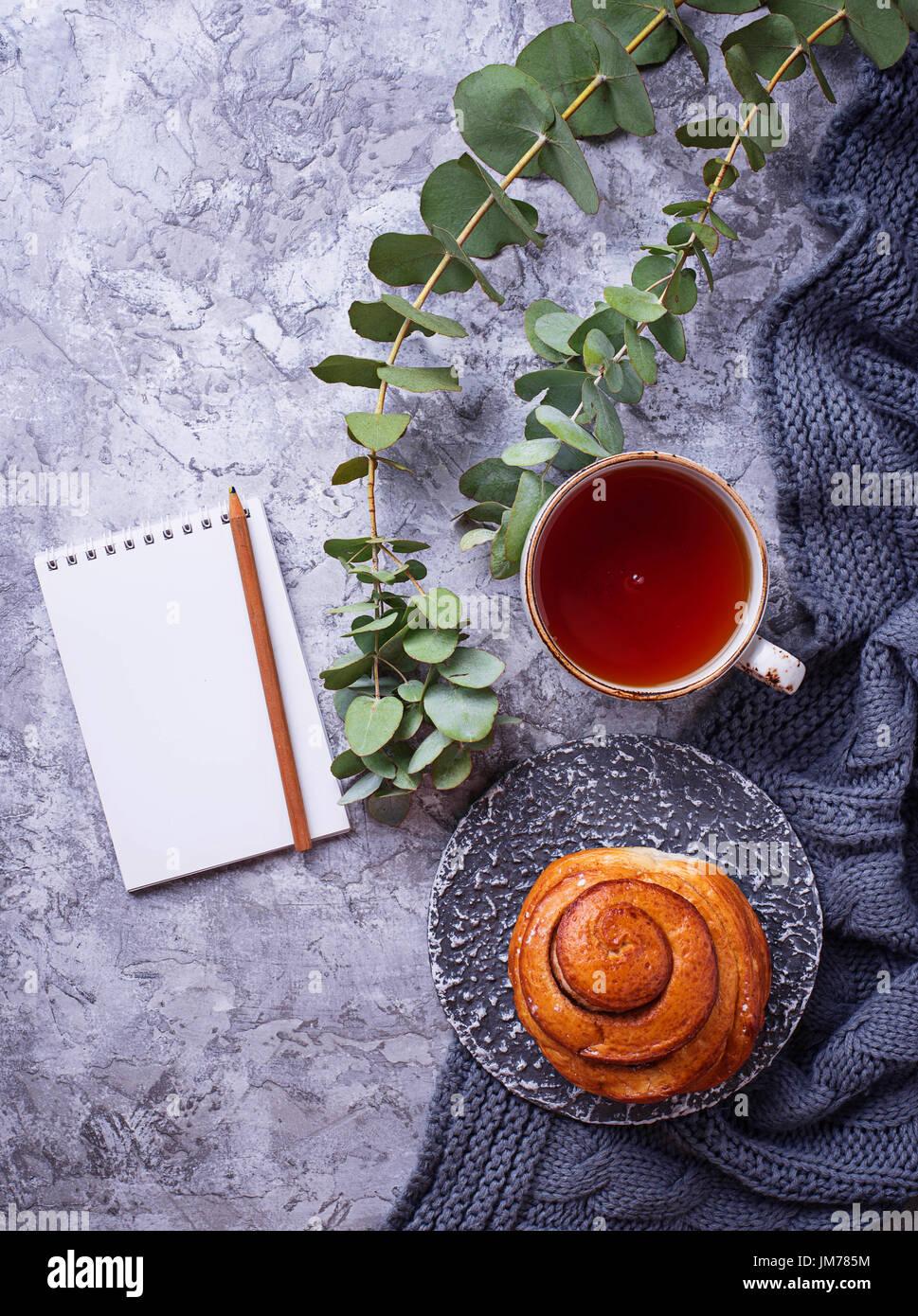 Espace de travail féminin avec bun, tasse de thé et ordinateur portable. Mise à plat, vue du dessus Photo Stock