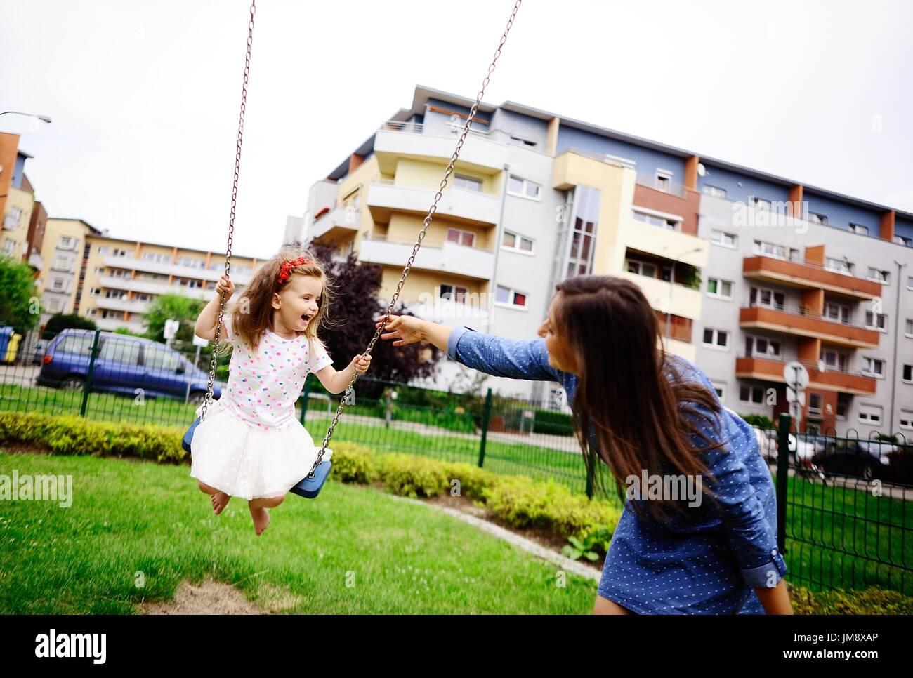 Jeune mère joue dans l'aire de jeux avec la petite fille. Femme secoue le bébé sur une balançoire. Serene journée d'été. Bonne humeur. Photo Stock