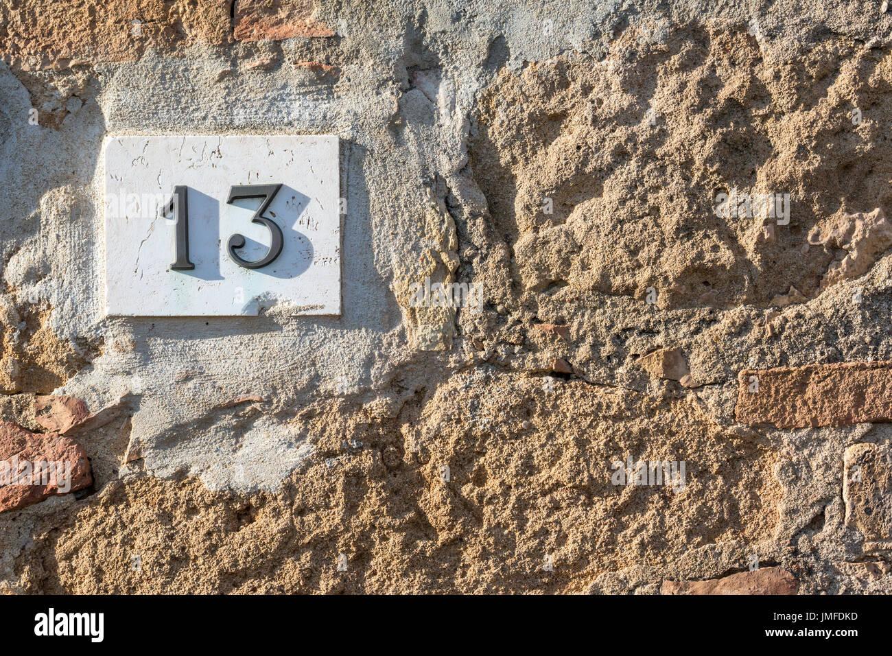 Signe de route sur une maison de la lecture du numéro treize fait de chiffres en métal sur un socle en marbre Photo Stock