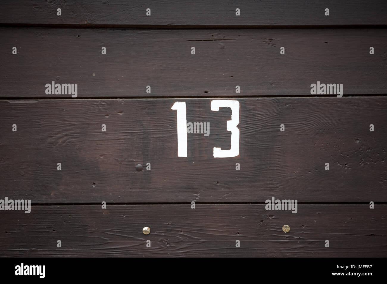 Signe de route sur une maison de la lecture du numéro treize peint avec peinture blanche sur panneau de bois Photo Stock
