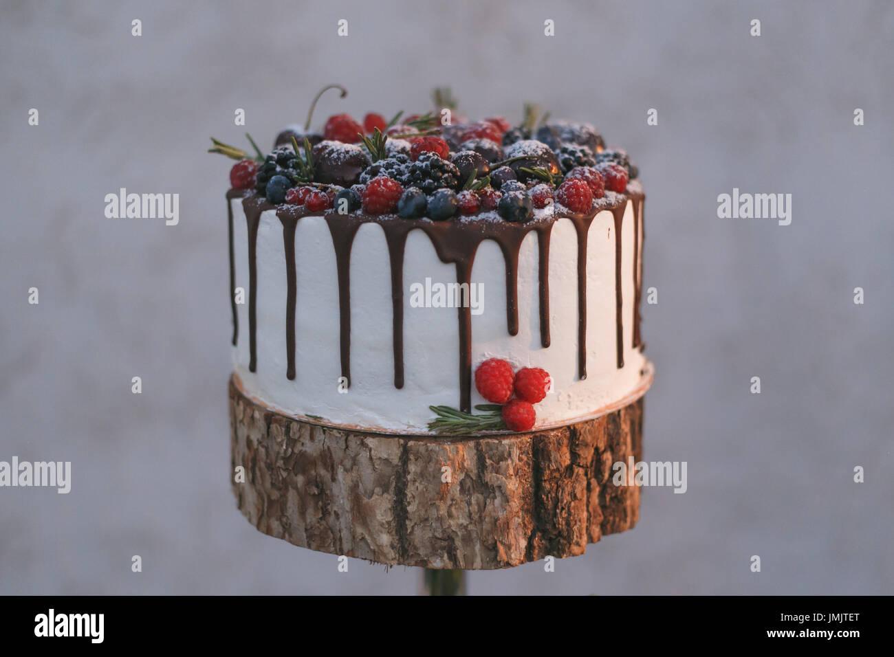 Un gâteau de mariage avec des baies, versé avec du chocolat sur une étagère en bois Photo Stock