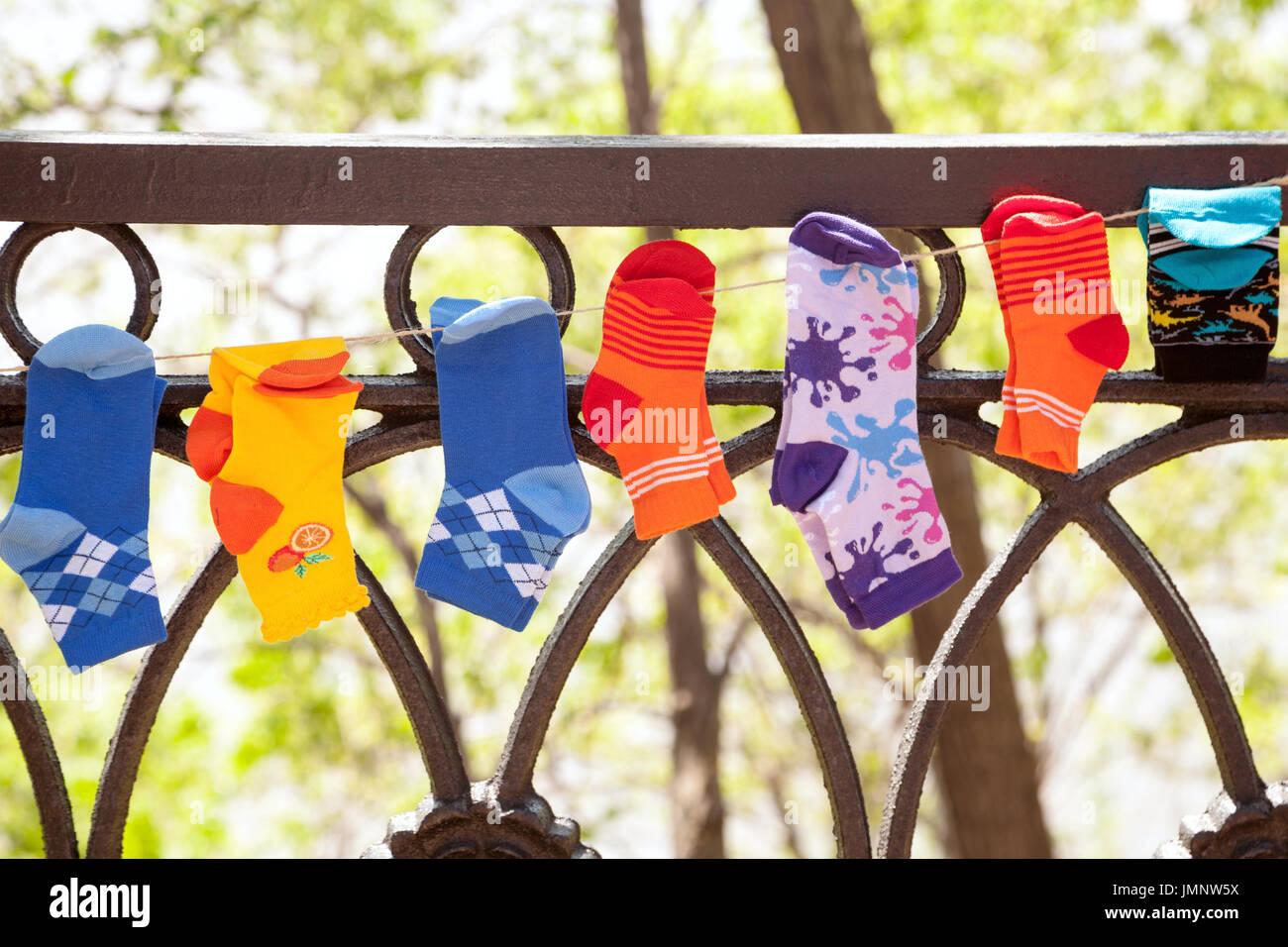 Divers chaussettes pour enfants colorés accrochés sur une ligne de lavage extérieur. De nombreuses petites chaussettes Banque D'Images