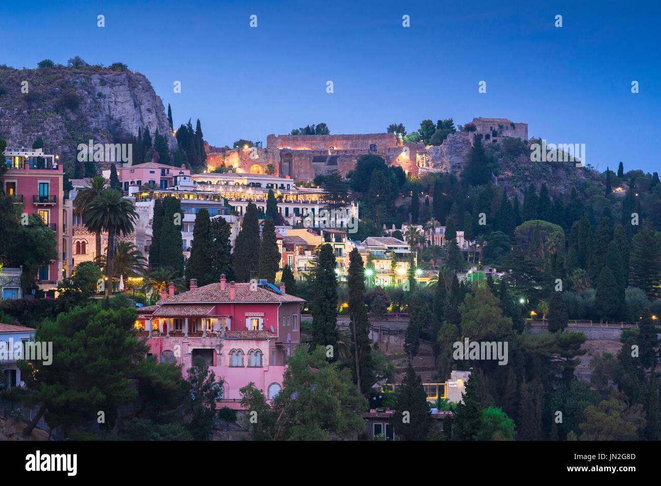La ville de Taormina en Sicile, le flanc de la ville de Taormina la nuit avec le théâtre grec antique allumé sur l'horizon, en Sicile. Photo Stock