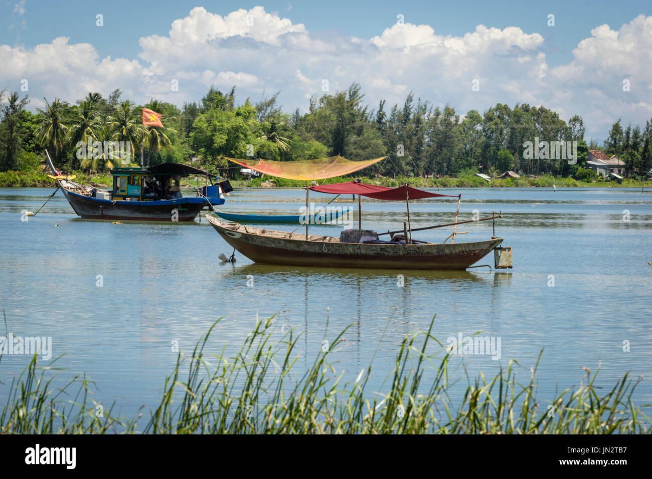 Bateau de pêche vietnamiens à l'ancienne ligne et bateau amarré sur la rivière Thu Bon à l'extérieur de Hoi An Vietnam Photo Stock