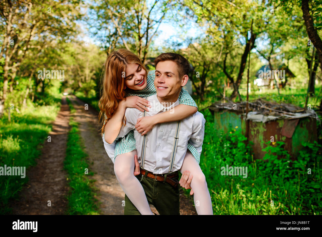 Portrait of young man giving woman piggyback. Photo Stock