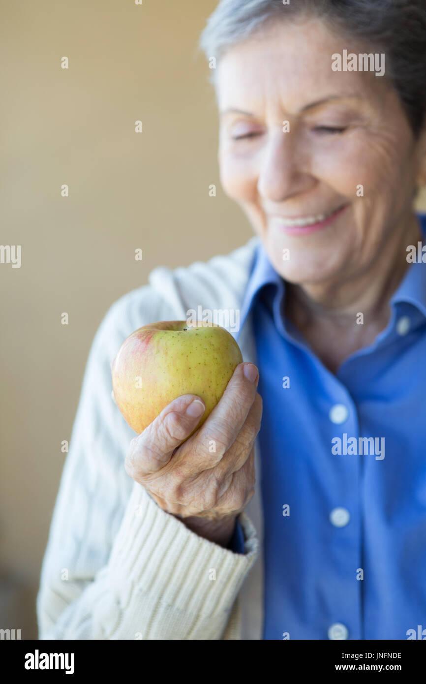Femme âgée mange une pomme. Photo Stock