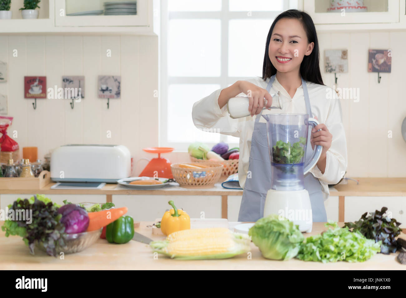 Smoothie aux légumes. Asian woman making green smoothies avec blender home en cuisine. Mode de vie sain manger cru concept portrait de jeune et belle Photo Stock